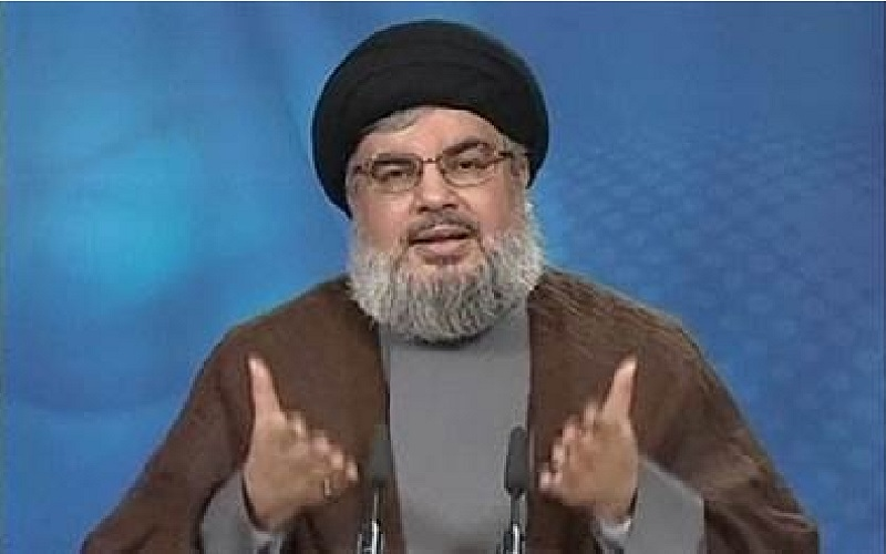 Hassan Nasrallah Gesturing during remote feed video onto large screen during Hezballah semi-annual pretense of readiness to defeat any Israeli assault as he remain in hiding presumably beyond the reach of Israeli drones and commandos. This enhances his appearance of constantly under threat by Israeli forces seeking to assassinate him. The likely truth is that Israel had no reason, desire or even bothered to draw up plans to do so. As far as whether Israel could find Hassan Nasrallah's various secreted locations, probably already have them pinpointed on some map just in case it becomes advantageous to remove Nasrallah from his position as the figurehead of Hezballah.